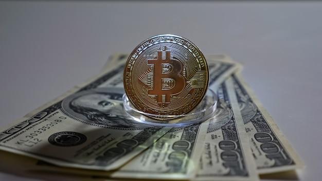 La pièce de monnaie bitcoin sur le support se dresse sur des billets d'un dollar sur fond blanc.