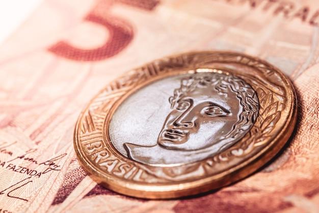 Une pièce de monnaie brésilienne sur un billet de banque brésilien de cinq reais en photo en gros