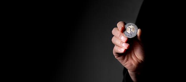 Pièce de monnaie crypto en argent neo dans la main masculine sur fond noir avec fond.