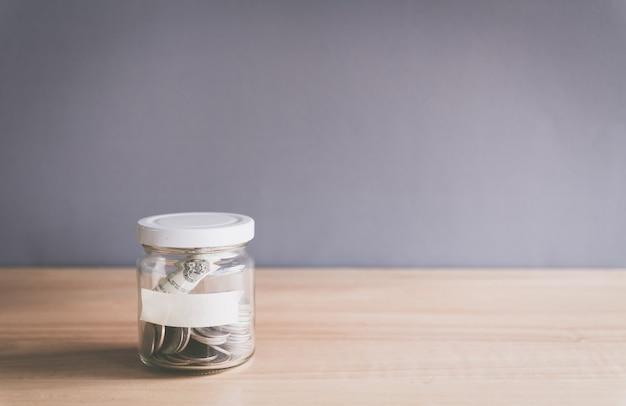 Pièce de monnaie dans un bocal en verre avec étiquette vide pour le texte sur le bureau en bois concept d'économie d'argent