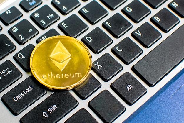 Pièce de monnaie golden ethereum avec le symbole ethereum sur un clavier d'ordinateur portable à côté de la touche entrée blockchain.