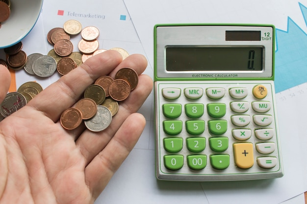 Pièce de monnaie sur une main masculine et calculatrice sur papier millimétré