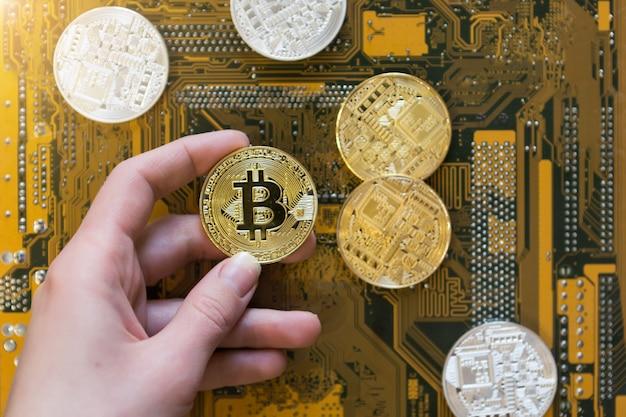 Pièce de monnaie d'or de bitcoin de crypto-monnaie dans la main de femme sur le fond de puce d'ordinateur. symbole de la crypto-monnaie et du concept de monnaie virtuelle électronique, vue de dessus à plat