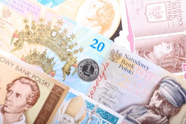 Pièce de monnaie polonaise en zloty sur fond de billets de banque polonais