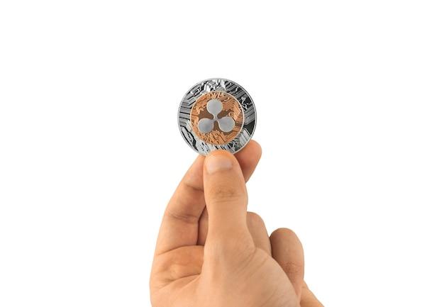 Une pièce d'ondulation en main isolée sur fond blanc, photo de crypto-monnaie