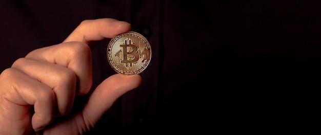 Pièce d'or bitcoin btc brillante dans la main masculine sur fond noir. bit crypto-monnaie. bannière avec espace de copie pour le texte.