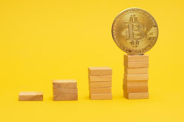 Pièce d'or bitcoin sur une échelle de blocs de bois.