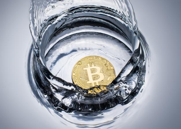 Pièce en or bitcoin avec éclaboussures d'eau.