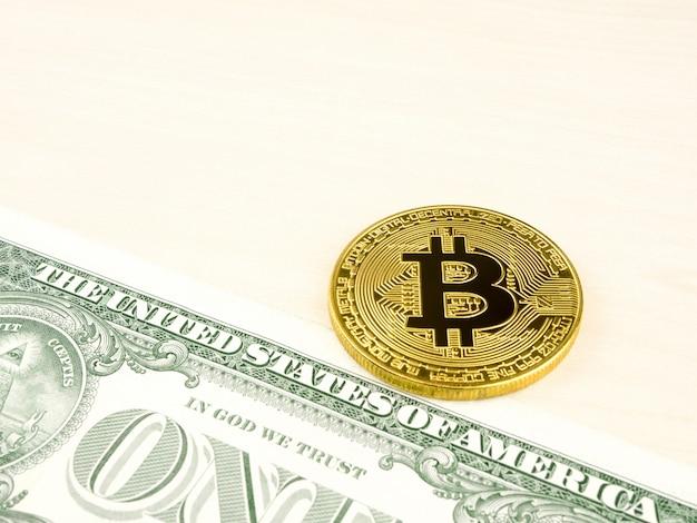 La pièce d'or bitcoin sur nos dollars se bouchent.