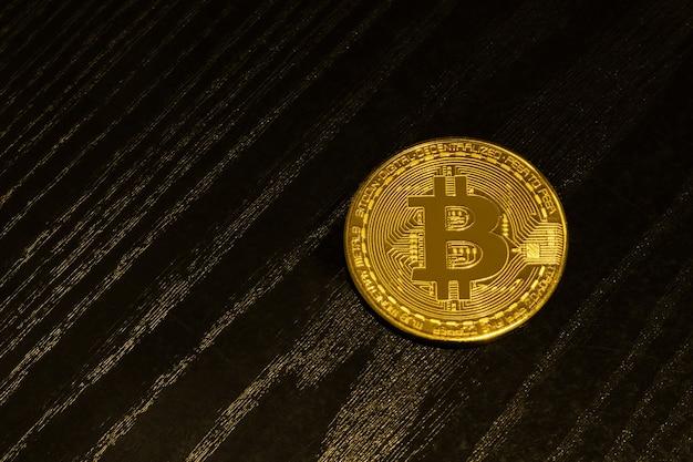 Pièce d'or bitcoin sur une planche en bois noire