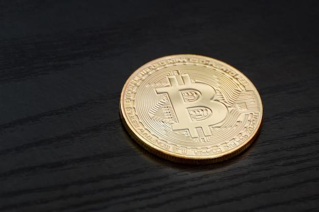 Pièce d'or bitcoin sur une surface en bois noire, concept d'entreprise