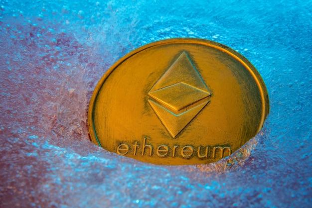 Pièce d'or ethereum, monnaie numérique en ligne gelée dans la glace bleue.
