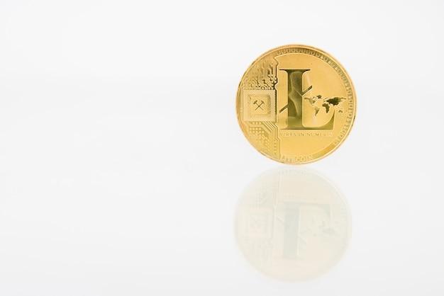 Pièce d'or litecoin avec réflexion sur la table, monnaie numérique en ligne.