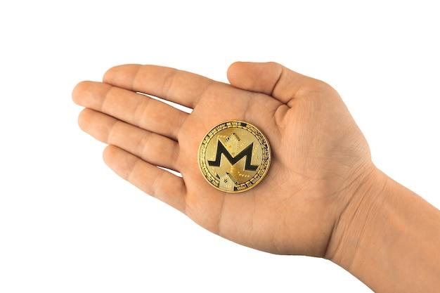Pièce d'or de monero dans la main masculine d'isolement sur le fond blanc, photo de pièce de monnaie de crypto-monnaie