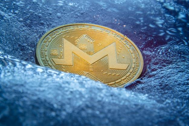 Pièce d'or monero, monnaie numérique en ligne gelée dans la glace bleue.