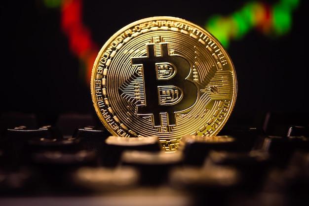 Une pièce d'or avec symbole bitcoin sur clavier d'ordinateur avec fond graphique stock.