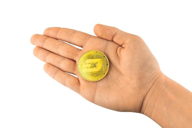 Pièce d'or de tiret dans la main d'isolement sur le fond blanc, photo de symbole de tiret de pièce de monnaie de blockchain de crypto-monnaie