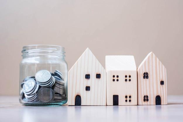 Pièce en pot de verre et modèle de maison en bois sur fond de table.