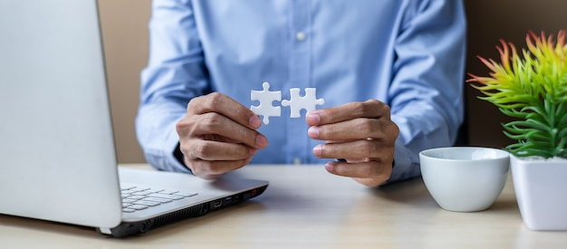 Pièce de puzzle reliant couple homme d'affaires main au bureau.