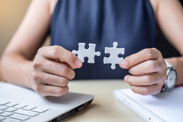 Pièce de puzzle reliant la main de femme d'affaires couple