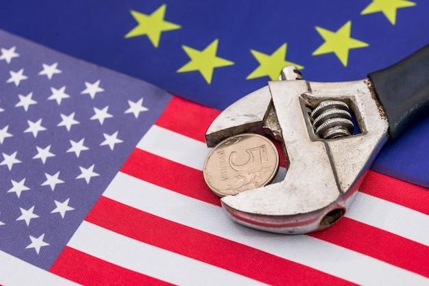 Pièce de rouble dans l'étau sur le drapeau de l'europe et de l'amérique
