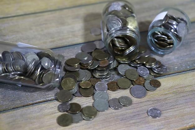 Pièces accumulées empilées dans des bocaux en verre sur le sol