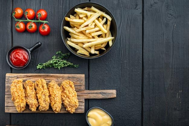 Pièces d'ailes de poulet frites sur bois noir