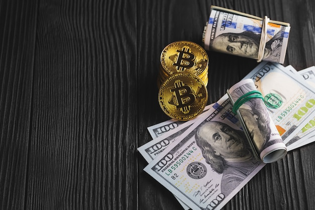 Pièces d'argent et d'or avec bitcoin, sur bois.
