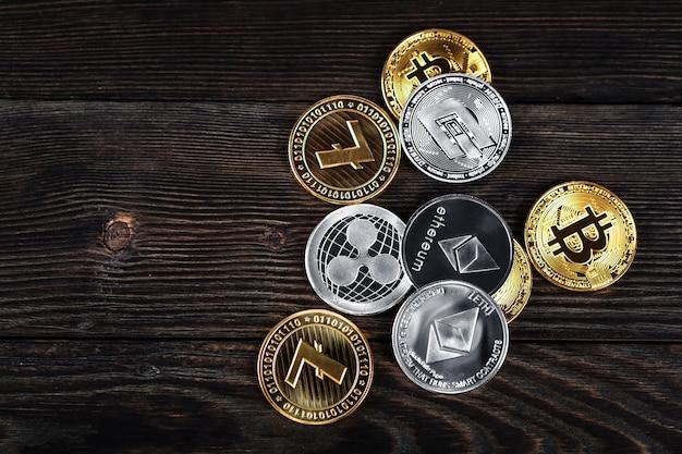 Pièces d'argent et d'or avec bitcoin, ondulation et symbole ethereum sur fond de bois.