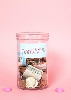 Pièces et billets dans un bocal en verre avec étiquette, dons financiers, organisme de bienfaisance, concept croissant de fonds.
