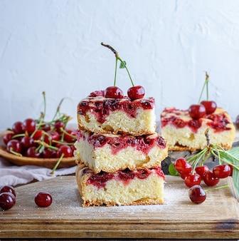 Pièces carrées d'une tarte aux biscuits avec des cerises sur une planche de bois blanche
