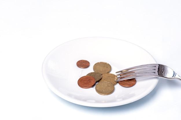 Pièces de cent euro sur une plaque blanche avec une fourchette sur un blanc