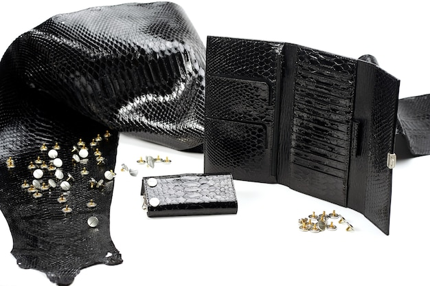 Des pièces de cuir noir glancy se trouvaient près du portefeuille de la femme avec de nombreux secteurs. ils ressemblent à de la peau de reptile. le matériau lisse repose sur le fond blanc. il y a aussi des clous métalliques à proximité.