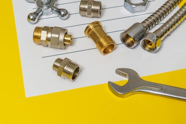 Pièces détachées plomberie et clé à molette gros plan sur la fiche pour notes et préparation d'un plan de réparation