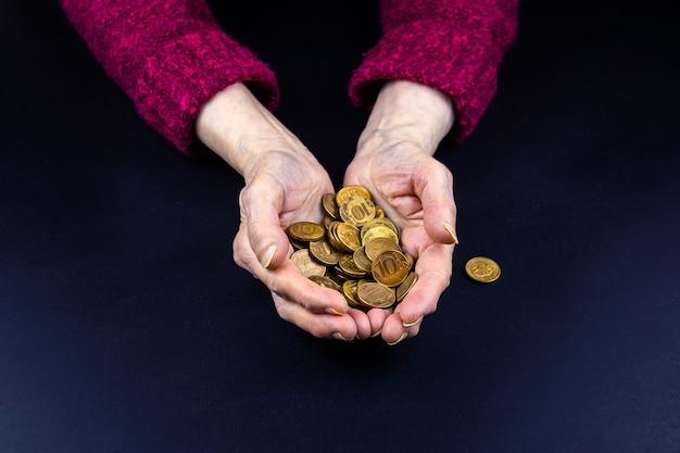 Des pièces de dix roubles sont versées entre les mains d'un retraité, le concept de pauvreté