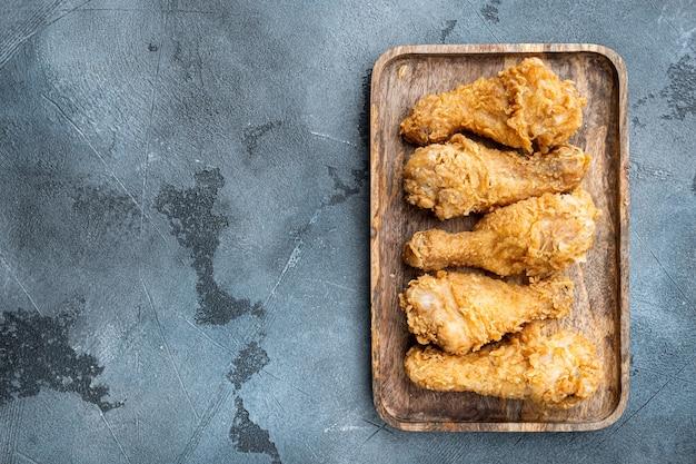 Pièces de drumctick de poulet pané du kentucky sur table grise, vue de dessus.
