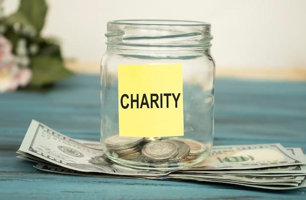 Pièces du monde dans un bocal en verre d'argent avec étiquette mot charité place sur table en bois naturel, espace vide pour le texte