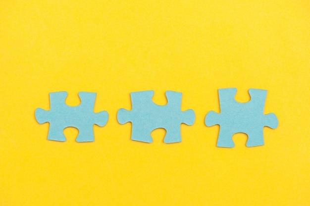 Pièces du puzzle bleu sur fond jaune