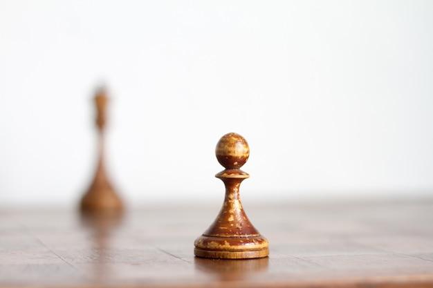 Pièces d'échecs en bois vintage sur un ancien échiquier.