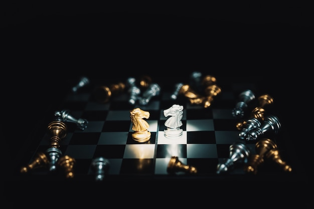 Les pièces d'échecs des chevaliers se font face pour une impasse sur l'échiquier.