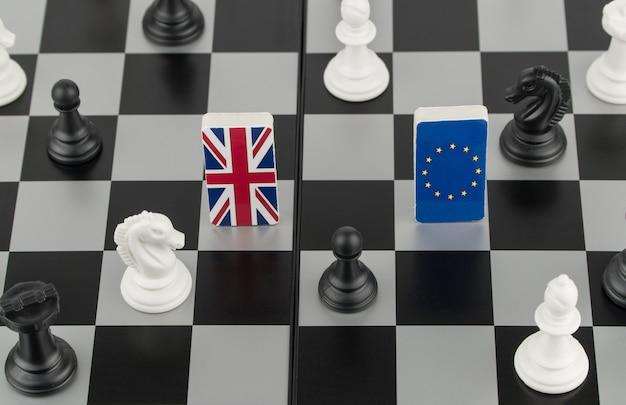 Pièces d'échecs et drapeaux de l'union européenne et de la grande-bretagne sur un échiquier jeu politique