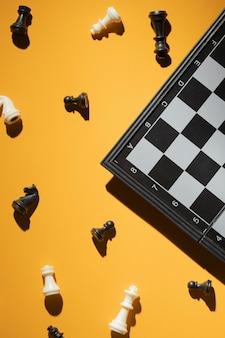 Pièces d'échecs et échiquier sur fond jaune