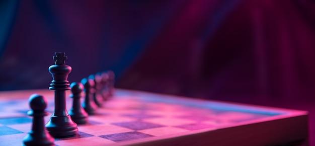 Pièces d'échecs sur un échiquier sur un fond sombre tourné dans des couleurs néon rose-bleu. la figure d'un échecs. gros plan.