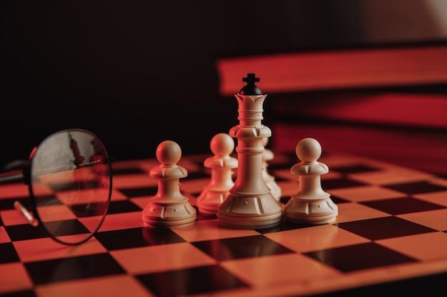 Pièces d'échecs sur l'échiquier avec des livres et des lunettes.