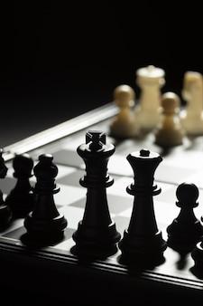Pièces d'échecs noires contre équipe blanche