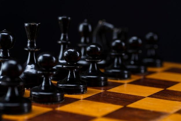 Pièces d'échecs noires sur un échiquier.