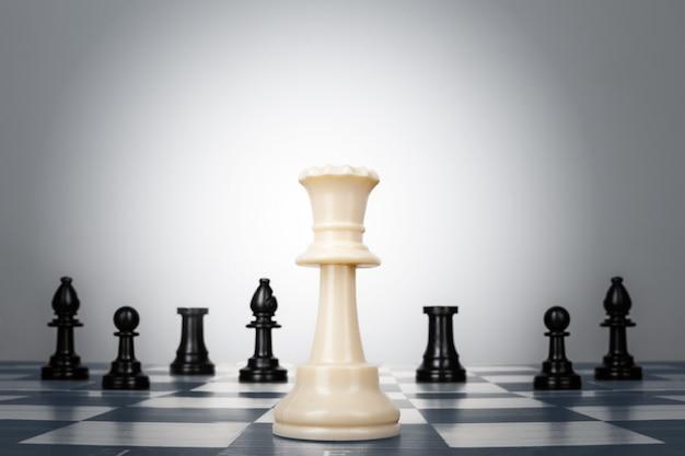 Une des pièces d'échecs reste contre le jeu de pièces d'échecs. stratégie, business
