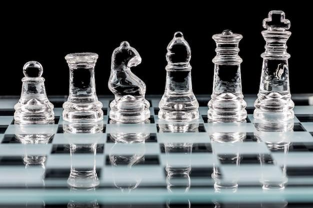 Pièces d'échecs en verre sur un échiquier en verre avec réflexion, sur fond noir.