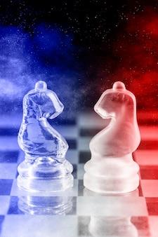 Pièces d'échecs en verre avec lumière bleue et rouge sur un échiquier en verre avec reflet, sur fond noir.