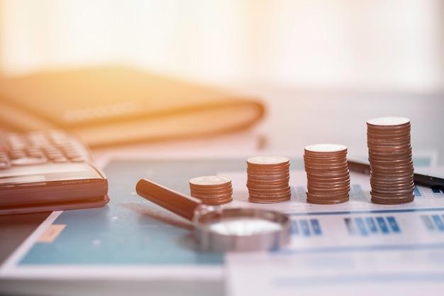 Pièces empilées sur le rapport financier avec une loupe et une calculatrice.